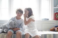 窓際に座って少年に耳打ちをする少女 24014000763  写真素材・ストックフォト・画像・イラスト素材 アマナイメージズ