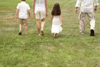 手を繋いで芝の上を散歩する家族