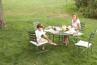 ガーデンテーブルで朝食を食べる母と息子 24014000796| 写真素材・ストックフォト・画像・イラスト素材|アマナイメージズ