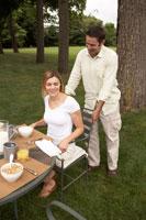 ガーデンテーブルの席に妻を座らせる夫
