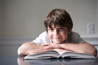 テーブルの上で本を開いて微笑む少年