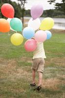 カラフルな風船をもって湖畔を走る少年 24014000826  写真素材・ストックフォト・画像・イラスト素材 アマナイメージズ