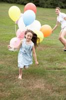 カラフルな風船をもって芝の上を走る少女と母 24014000831  写真素材・ストックフォト・画像・イラスト素材 アマナイメージズ