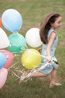 カラフルな風船をもって芝の上を走る少女 24014000832  写真素材・ストックフォト・画像・イラスト素材 アマナイメージズ
