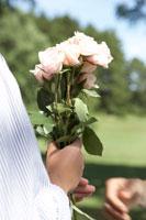 バラの花束を手渡す女性の手元