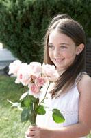 バラの花束を持つ少女