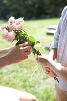 子供たちからバラを受け取る母親の手元