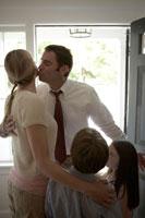 玄関で妻にキスをする夫と寄り添う子供たち