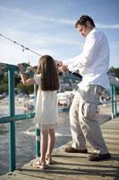 桟橋で釣りをする父と娘 24014000880| 写真素材・ストックフォト・画像・イラスト素材|アマナイメージズ