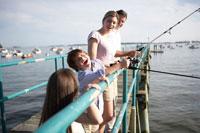 桟橋で釣りをする家族