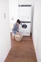 洗濯機に洗濯物を入れる女性
