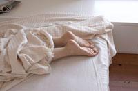 ベッドに寝る女性の足 24014000919| 写真素材・ストックフォト・画像・イラスト素材|アマナイメージズ