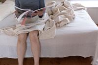 ベッドに座り雑誌を読む女性の足元