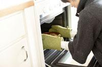 オーブンを開ける女性