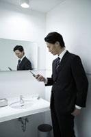 トイレで携帯をみる男性社員