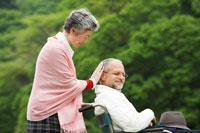 車椅子のシニア男性に付添うシニア女性