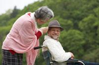 車椅子のシニア男性を労わるシニア女性