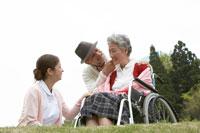 車椅子のシニア女性に付添う男性と看護師