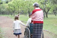 車椅子を押すシニア女性と子供