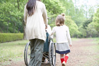 車椅子を押す女性と子供