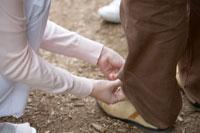 男性のパンツ丈を直す看護師