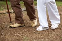 シニア男性と寄添う看護師の足元