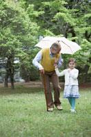 傘をさすシニア男性と散歩する子供