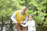 杖をつくシニア男性と散歩する子供