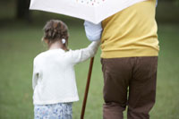 傘をさすシニア男性と子供の背中