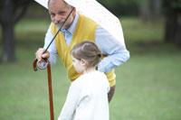 傘をさすシニア男性と子供