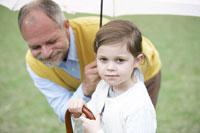 杖をもつ子供と見守るシニア男性