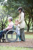 シニア女性が乗る車椅子を押す娘と孫