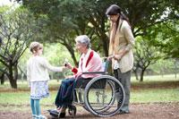 車椅子に座るシニア女性に花をあげる子供