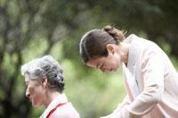 シニア女性が座る車椅子を押す看護師