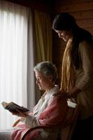 読書するシニア女性に寄添う女性