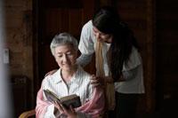 読書するシニア女性に寄添う女性 24015000131  写真素材・ストックフォト・画像・イラスト素材 アマナイメージズ
