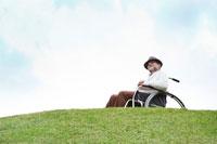 丘の上で車椅子に座るシニア男性