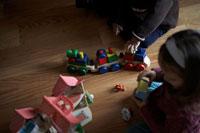 木のおもちゃで遊ぶ子供2人