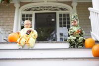 着ぐるみを着て階段に座る子供2人