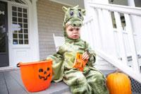 ドラゴンの衣装をつけ座る男の子