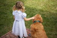 犬と一緒に佇む女の子の後ろ姿