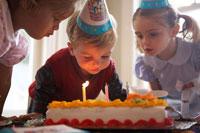 ケーキのろうそくを吹き消す子供3人