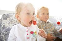 ソファでキャンディーをなめる男の子と女の子