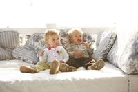 ソファでキャンディーをなめる男の子と女の子 24015000450| 写真素材・ストックフォト・画像・イラスト素材|アマナイメージズ