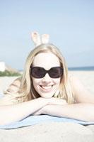 ビーチで寝そべるサングラス女性
