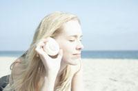 貝殻の音を聴く女性