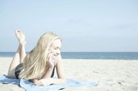 携帯電話で話すビーチにいる女性