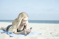 ビーチで携帯をチェックする女性
