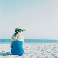 ビーチに座る帽子姿の女性の後姿 24016000204| 写真素材・ストックフォト・画像・イラスト素材|アマナイメージズ