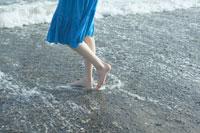 ビーチを歩く女性の足元